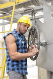 Young worker fixing industrial valve with wrench Stock Images