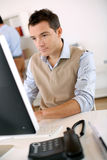 Young worker in front of computer Stock Photography