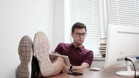Young worker in glasses holding the keyboard on his legs typing and looking at the screen of the computer in office with. Young office worker in glasses holding stock footage
