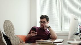 Young worker in glasses relaxing with his legs on the table modern office using phone. Bored manager surfing in internet. Shot in 4k stock video footage
