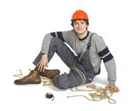 A young worker in grey uniform tied up with rope on white isolated background. Royalty Free Stock Photography