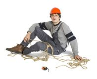 A young worker in grey uniform tied up with rope on white isolated background. Royalty Free Stock Photos
