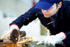 Young worker grinding a metal plate. Worker while grinding a metal plate Stock Photography