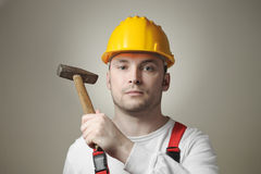 Young worker with hammer. Unhappy young worker with a hammer Stock Image