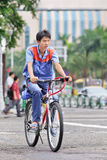 Young worker on his bike in the city center, Zhuhai, China Royalty Free Stock Images