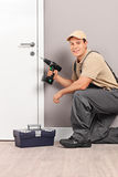 Young worker installing a door with a screwing drill Royalty Free Stock Photography