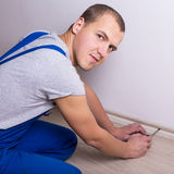 Young worker installing new skirting board at home Royalty Free Stock Image