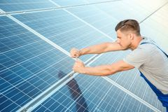 Young worker installing solar panels. Outdoors Stock Photo