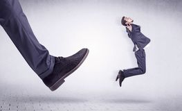 Young worker kicked out by big foot. Small young businessman kicked out by a big black shoe Royalty Free Stock Images