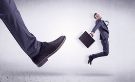 Young worker kicked out by big foot. Small young businessman kicked out by a big black shoe Royalty Free Stock Image