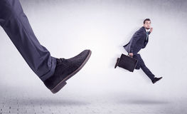 Young worker kicked out by big foot. Small young businessman kicked out by a big black shoe Stock Photos