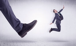 Young worker kicked out by big foot. Small young businessman kicked out by a big black shoe Stock Images