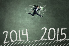 Young worker leaps through number 2014 to 2015. Entrepreneur running above number 2014 to 2015 against a blackboard background to achieve her success in the Stock Photo