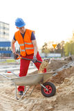 Young worker loading a wheelbarrow. Young building worker loading a wheelbarrow Stock Photos