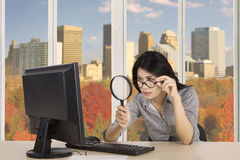 Young worker looking at computer with magnifier Stock Photos
