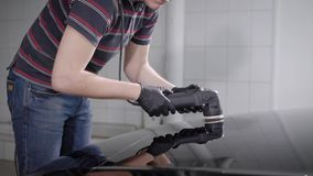 Young worker man is processing car surface by electrical polishing machine in a workshop. Young worker man is processing car surface by electrical polishing stock video footage