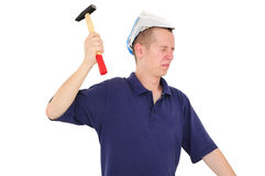 Young worker nailing with hammer. Young man with paper hat nailing with hammer Stock Photo