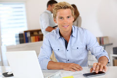 Young worker in office looking at camera stock image