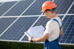 Young worker in overall looking in drawings at solar power station. Employee in blue overall and orange helmet, looking in technical documentation Royalty Free Stock Photos