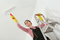 Young worker paint ceiling in a room Stock Image