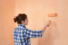 Young worker paint wall in a room to orange Stock Photo