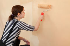 Young worker paint wall in a room to orange Royalty Free Stock Photography