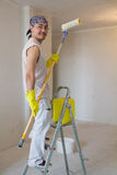 Young worker painting ceiling with painting roller Royalty Free Stock Images