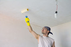 Young worker painting ceiling with roller. Young worker painting ceiling with painting roller Royalty Free Stock Image