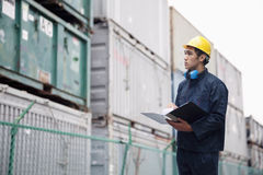 Young worker in protective work wear examining cargo in a shipping yard royalty free stock images