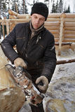 Young worker removes  bark from log using electric planer. Stock Photo