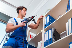 The young worker repairing shelves in office Stock Photography