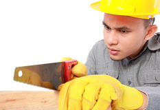 Young worker with saw. Young worker sawing wood isolated on white background Stock Photos