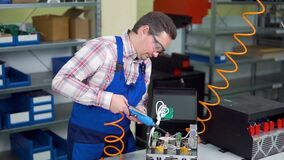 Young worker in shirt and overalls assembles electronic components in a hi tech factory