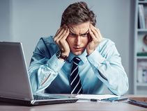 Young worker sitting in his office thinking. Business concept. Close up Royalty Free Stock Photos