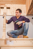 A young worker sitting and holding cordless drill. A young worker sitting on wooden ladder  and holding cordless drill Stock Photography
