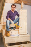 A young worker sitting on ladder and holding one step Royalty Free Stock Images