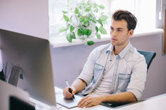Young worker sitting in an office at the computer. Freelancer in a blue shirt. The designer sits in front of window in Royalty Free Stock Photography