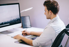 Young worker sitting in an office at the computer. Freelancer in a blue shirt. The designer sits in front of window in Stock Photo