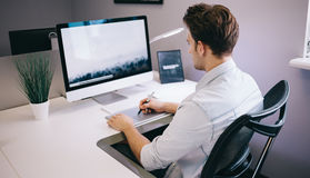 Young worker sitting in an office at the computer. Freelancer in a blue shirt. The designer sits in front of window in Stock Photos