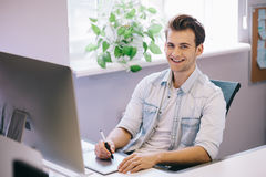 Young worker sitting in an office at the computer. Freelancer in a blue shirt. The designer sits in front of window in Stock Images