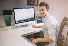 Young worker sitting in an office at the computer. Freelancer in a white shirt. The designer sits in front of window in stock photography