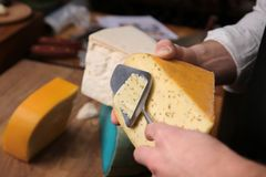 Young worker slicing cheese. In shop Royalty Free Stock Photos