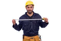 Young worker smiling. Smiling beard young worker holding tape measure, man wearing workswear and belt equipment, isolated on white background Stock Photos
