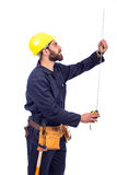 Young worker smiling. Smiling beard young worker measuring by tape measure and looking up, man wearing workswear and belt equipment, isolated on white background Stock Photo