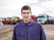 Young worker standing in front of trucks Royalty Free Stock Photo