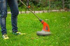 Young worker with a string lawn trimmer mower cutting grass in a blurred nature background.  Stock Images