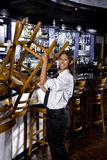 Young worker taking down bar stools Stock Photography