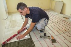 Young worker tiler installing ceramic tiles using lever on cement floor with heating red electrical cable wire system. Home. Improvement, renovation and royalty free stock photo