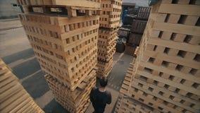 A young worker in uniform walks between wooden pallets in distribution outdoor warehouse. Slow motion. view from above. A young worker in uniform walks between stock footage