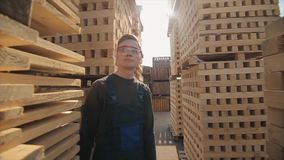 A young worker in uniform walks between wooden pallets in distribution outdoor warehouse. Slow motion. Wide view stock video footage